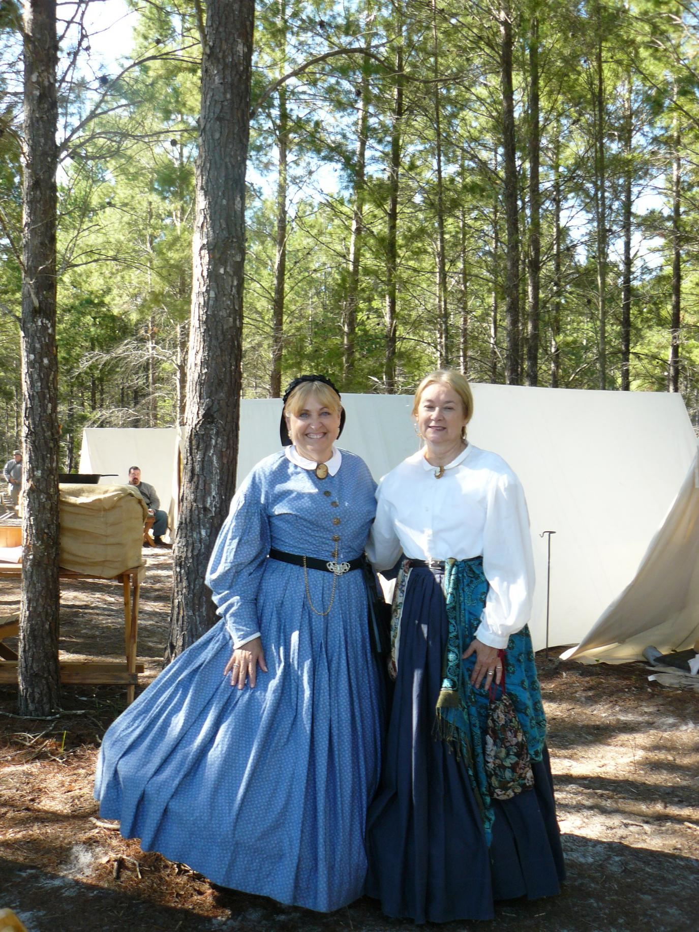 Two women wearing Dresses from the late 1800's with corsets on as well